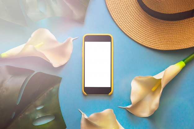 Smartphone with straw hat, tropical leaves monstera and white callas, on light blue backgr