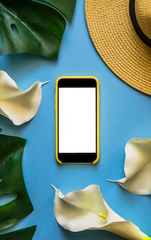 Smartphone with straw hat, tropical leaves monstera and white callas