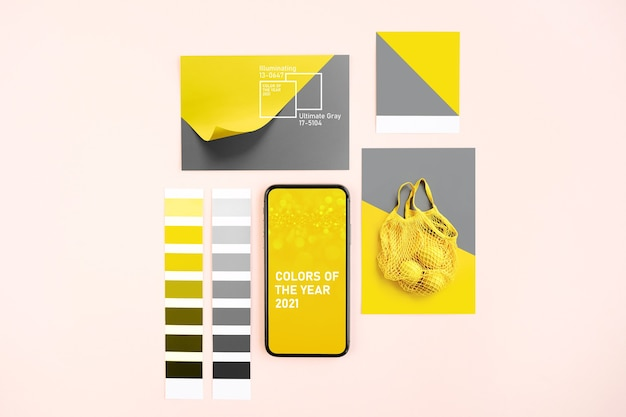 Smartphone with ultimate grey and illuminating colors of the year 2021  and fashion colour swatches. collage with color trend palette.