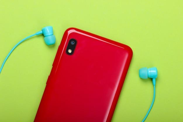 緑の真空イヤホン付きスマートフォン