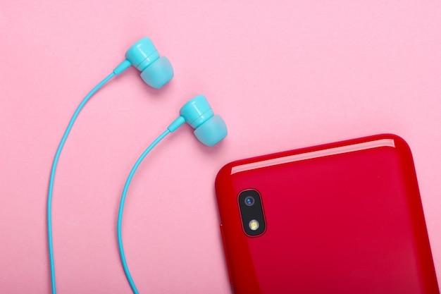 ピンクの真空イヤホン付きスマートフォン