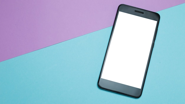 Smartphone with white screen on colored paper minimalism background.