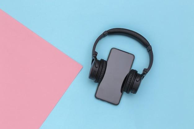 ピンクブルーのパステルカラーの背景にワイヤレスステレオヘッドフォンを搭載したスマートフォン。上面図