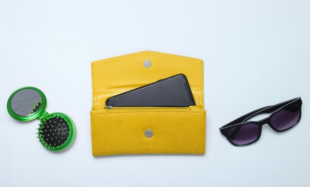 Smartphone in yellow leather wallet, sunglasses, mirror hairbrush