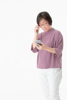 Старая азиатская женщина смотря к экрану smartphone и выглядеть как смущает и тревожится.