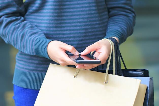 Рука молодой женщины держа smartphone и хозяйственные сумки с стоять на универмаге