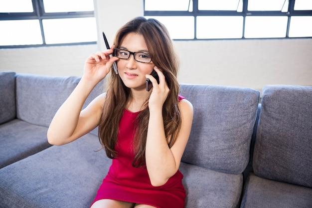 Коммерсантка сидя на софе и говоря на smartphone в офисе