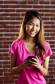 Усмехаясь азиатская женщина используя smartphone на кирпичной стене