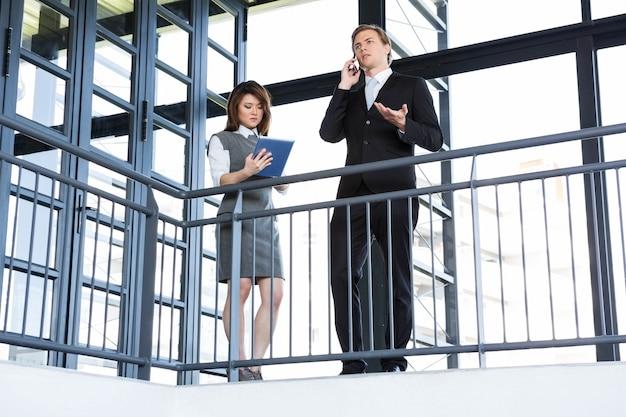 Бизнесмен говоря на smartphone и коммерсантке используя цифровую таблетку в офисе