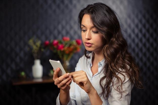 Творческая коммерсантка используя ее smartphone