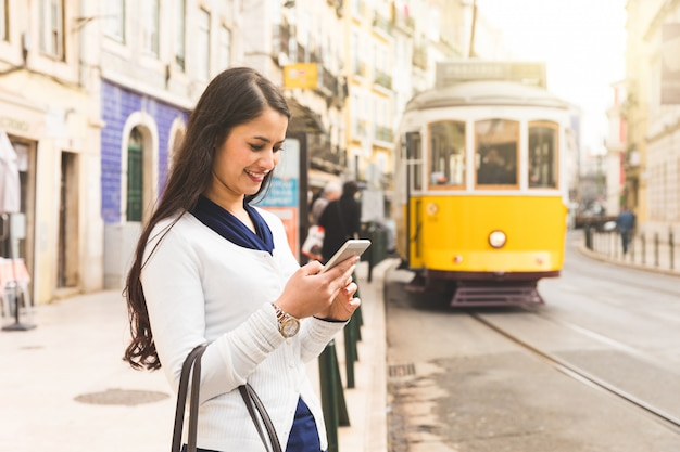 Турист женщины в лиссабоне проверяя расписание трамвая на ее smartphone