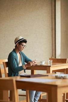 Молодой азиатский мужской битник сидя на таблице в кафе и используя smartphone