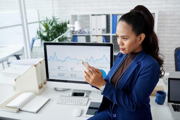 Молодая азиатская женщина в костюме сидя на столе в офисе и используя smartphone