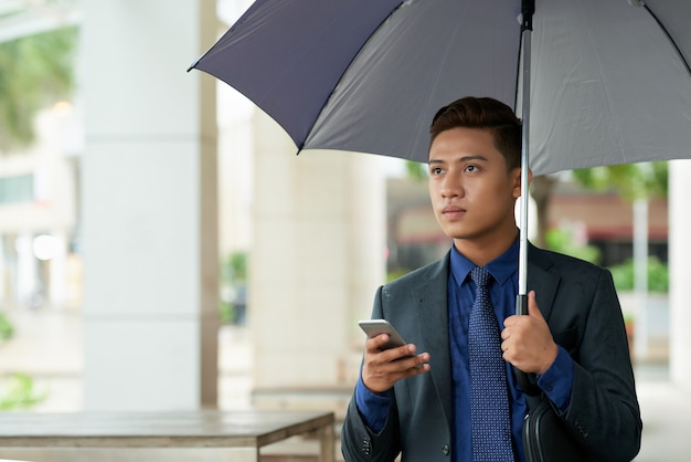Молодой азиатский бизнесмен с зонтиком стоя на улице с smartphone и смотря прочь