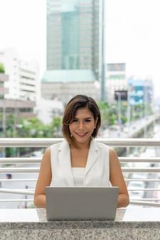 Красивая азиатская женщина усмехаясь в одеждах бизнес-леди используя портативный компьютер и smartphone
