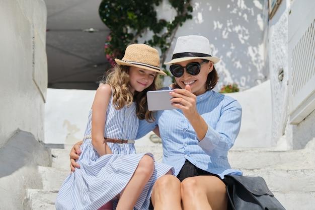 Ребенок матери и дочери сидя на белых шагах с smartphone