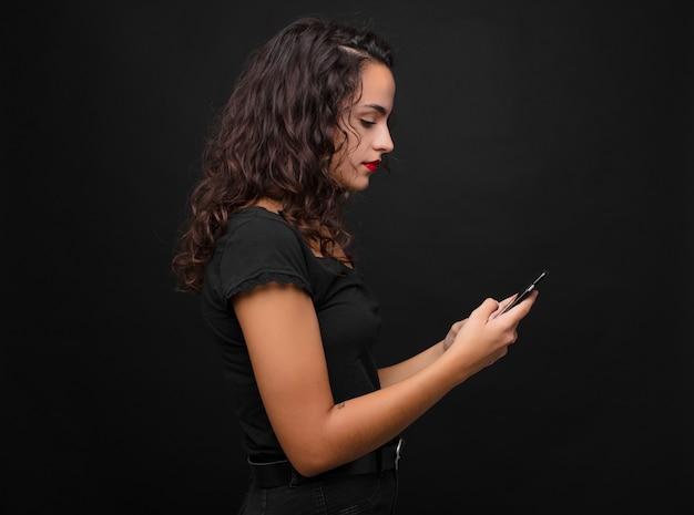 Молодая милая женщина на виде профиля смотря, что скопировать космос вперед, думающ, воображающ или мечтать держащ smartphone