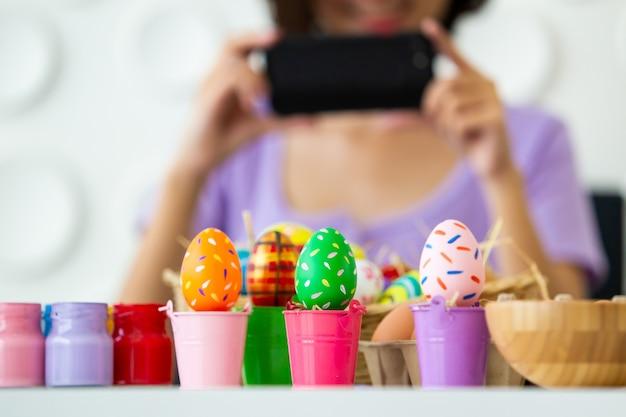 Азиатская молодая милая женщина наслаждается сделать фотографию к красочному пасхальному яйцу фантазии используя smartphone.