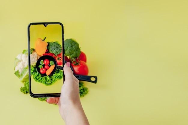 Девушка фотографируя вегетарианская еда на таблице с ее smartphone. веганские и здоровые концепции.