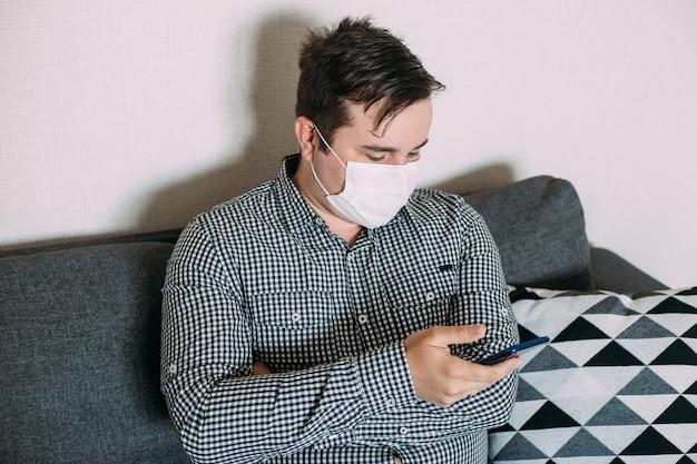 Маска человека нося работая с smartphone работая от домашнего офиса