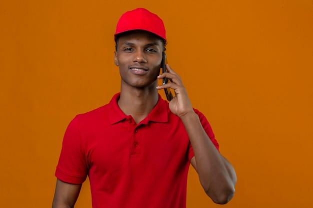 Молодой афро-американский работник доставляющий покупки на дом нося красную рубашку поло и крышку говоря smartphone смотря уверенно над изолированным апельсином