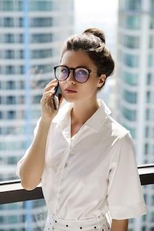 Молодая коммерсантка используя smartphone в ее офисе