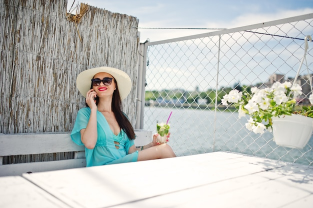 Шляпа и солнечные очки милой молодой дамы нося с коктеилом используя ее smartphone пока сидящ озером.