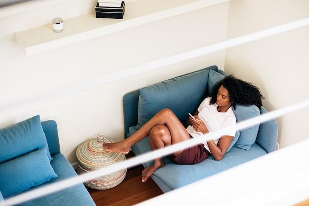 Жизнерадостная афро-американская женщина печатая на smartphone пока отдыхающ дома
