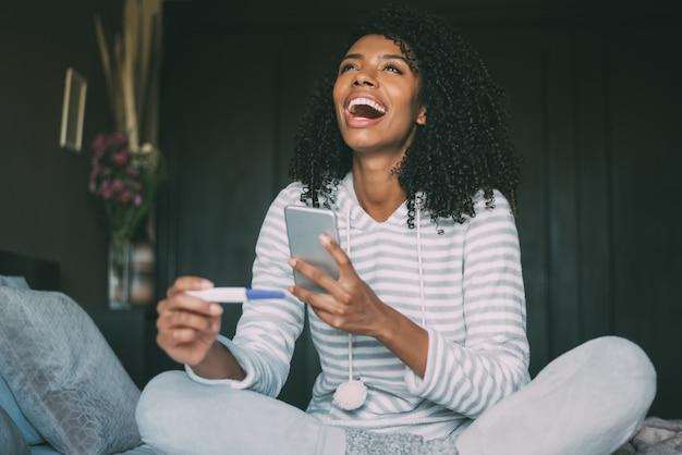 Счастливая чернокожая женщина с тестом на беременность и smartphone на кровати
