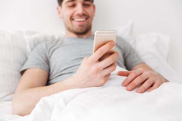 Счастливый человек брюнет лежа на кровати пока использующ smartphone