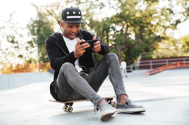Молодой африканский человек с скейтбордом используя smartphone