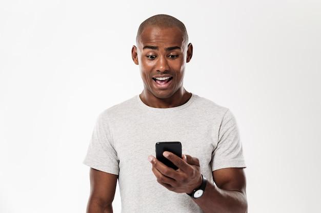 Удивленный африканский человек используя smartphone