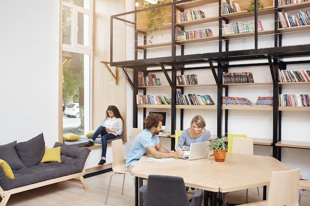 Большая современная библиотека утром. два человека сидят, глядя в монитор ноутбука, говорить о запуске проекта. девушка сидя на книге чтения подоконника на smartphone тратя время перед изучением.