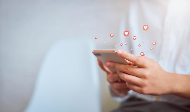 Рука женщины используя smartphone и показывает значок социальных средств массовой информации сердца. концепция социальной сети.