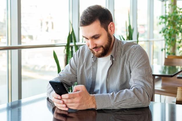 Смартфон текстовых сообщений. привлекательный бородатый кавказский бизнесмен используя smartphone сидя в офисе.