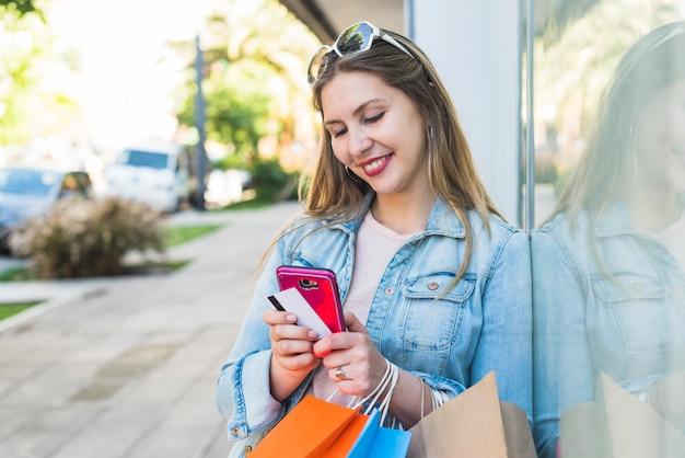 Счастливая женщина стоя с хозяйственными сумками, smartphone и кредитной карточкой снаружи