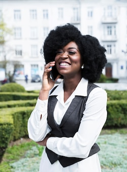 Портрет африканской счастливой молодой коммерсантки говоря на smartphone