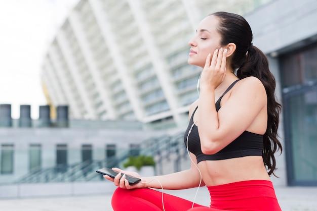 Молодая женщина спортсмена с smartphone