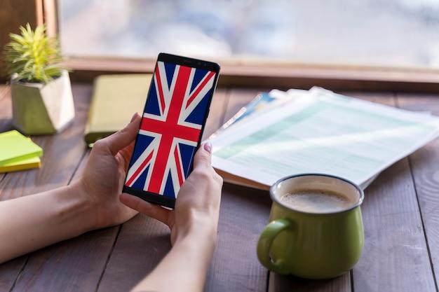 Женщина конца-вверх с smartphone и кофейной чашкой