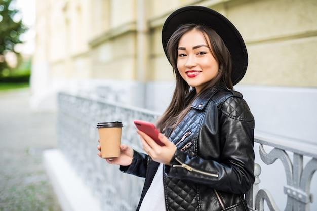 Молодая азиатская женщина с smartphone стоя против улицы с телефоном и чашкой кофе