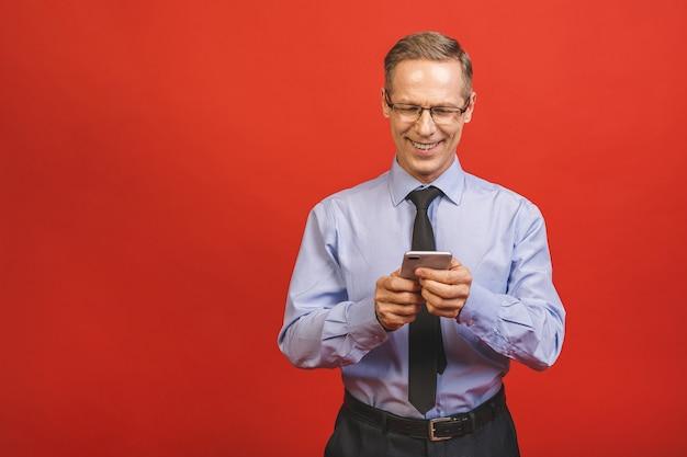 Расслабленный старший бизнесмен в официально печатая сообщении на smartphone изолированном на красной стене. портрет счастливого зрелого бизнесмена используя сотовый телефон. удовлетворенный лидер, проверка почты с копией пространства.
