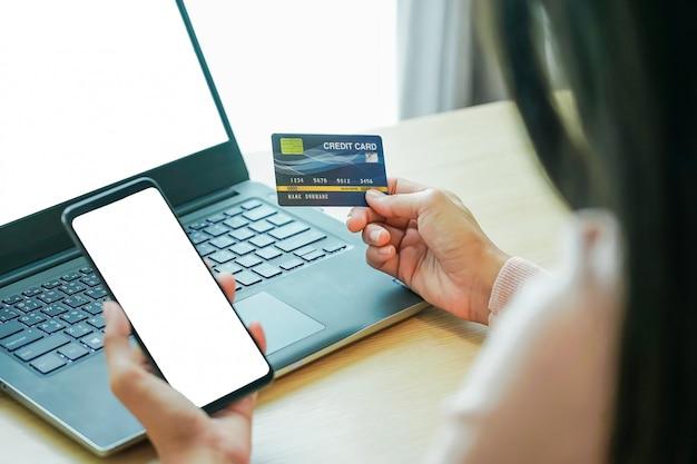 Азиатские руки молодой женщины держа кредитную карточку и используя smartphone компьтер-книжки