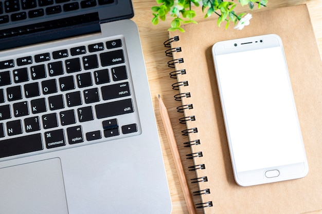 Компьтер-книжка с smartphone на дереве тетради, карандаша и цветочного горшка на деревянной предпосылке, таблице офиса взгляд сверху.