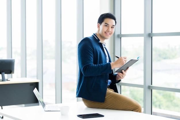 Думая о азиатский молодой бизнесмен работая с прочитанным примечанием записанным в тетради и портативном компьютере бизнес-плана, smartphone сидит на таблице в комнате офиса.