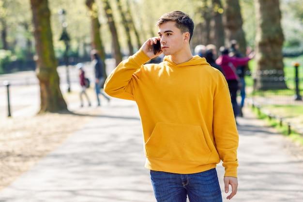 Молодой городской человек используя smartphone гуляя в улицу в городском парке в лондоне.