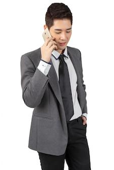 Счастливый молодой бизнесмен работая с smartphone в костюме смотря камеру, изолированную концепцию