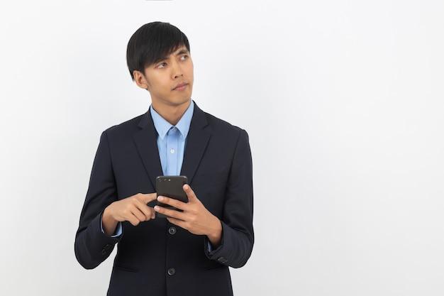 Молодой красивый азиатский бизнесмен играя smartphone и думая
