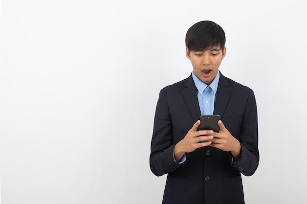 Молодой красивый азиатский бизнесмен играя smartphone с удивительно лицом