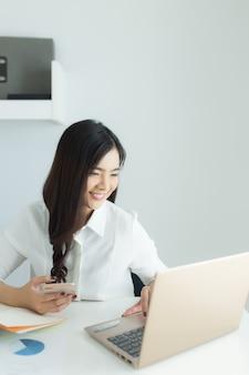 Молодая азиатская бизнес-леди работая на ее smartphone и компьтер-книжке на рабочем месте.