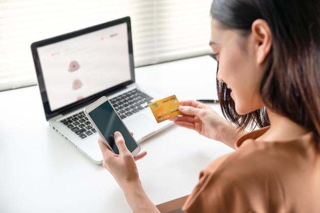Красивая азиатская молодая женщина используя кредитную карточку с компенсацией smartphone для онлайн покупок в вебсайте на компьтер-книжке